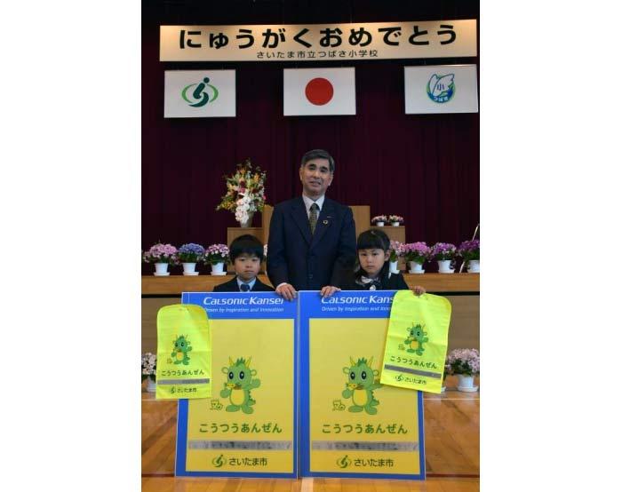 ランドセルカバーを贈られた新入学生代表(左、右)とカルソニックカンセイ・ジェネラルサポート部・渉外担当部長の金井浩氏(中央)