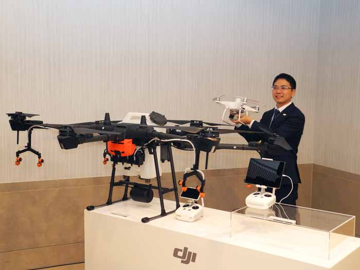 「P4 MULTISPECTRAL」を手に持つDJIジャパンの呉韜社長。手前の大きなドローン が「AGRAS T16」