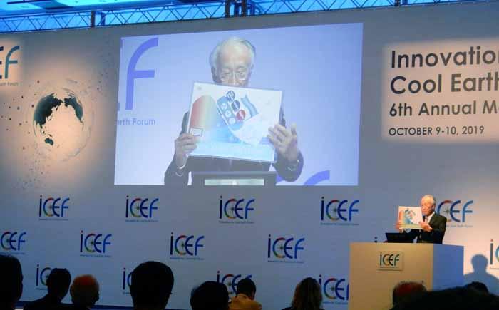 ICEF2019会合の成果を語る田中運営委員長。ステートメントの内容を表現したインフォグラフィックを示した