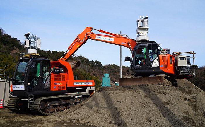 遠隔操作で掘削した土を積み込む油圧ショベル(写真右)とクローラキャリア(写真左)