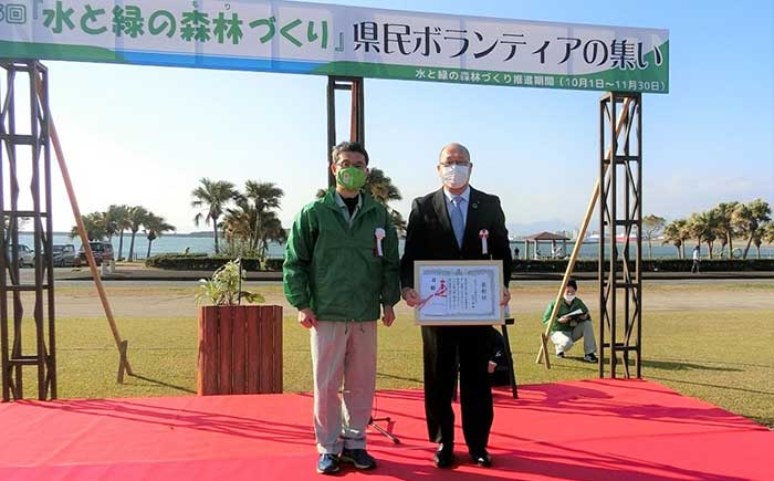 「水と緑の森林づくり」県民ボランティアの集いで宮崎県・河野知事(左)から表彰状を授与される宮崎工場・石田工場長(右)。